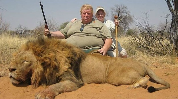 photo of 2 hunters with weapons in hand hovering over slain lion